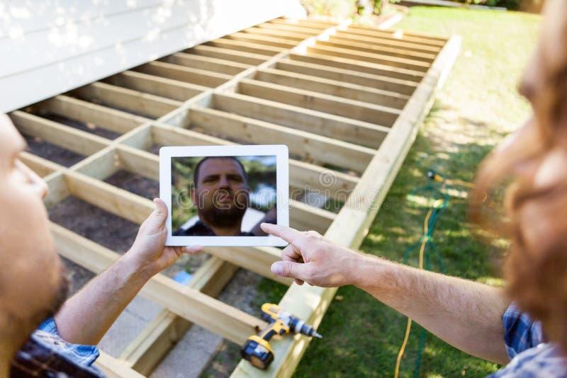 Carpinteiros que usam a tabuleta de Digitas na construção fotos de stock royalty free