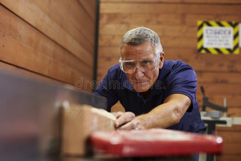 Carpintería Woodshop de Using Plane In del carpintero fotos de archivo