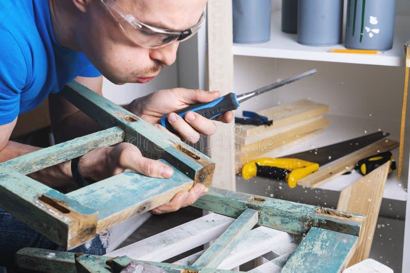 Carpinter?a: el amo de los muebles restaura el taburete viejo, dilapidado Primer de la mano de un hombre imágenes de archivo libres de regalías