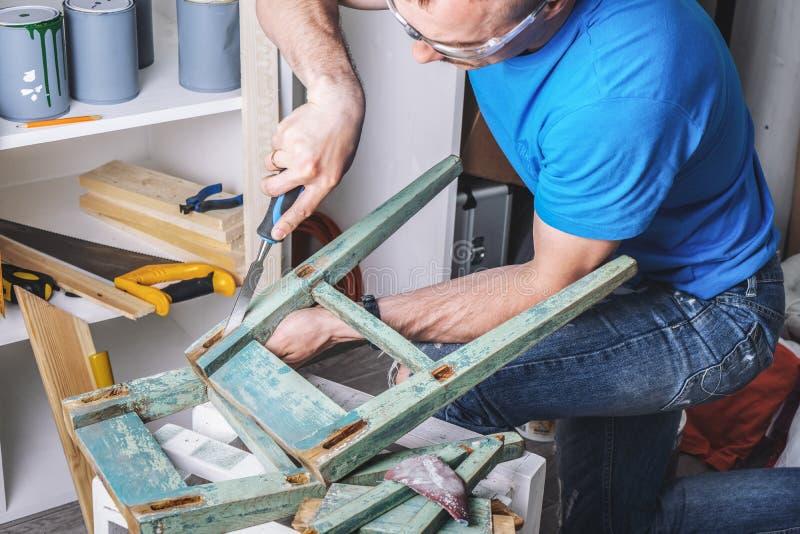 Carpinter?a: el amo de los muebles restaura el taburete viejo, dilapidado Primer de la mano de un hombre foto de archivo libre de regalías