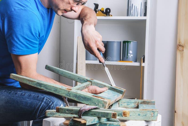 Carpinter?a: el amo de los muebles restaura el taburete viejo, dilapidado Primer de la mano de un hombre foto de archivo