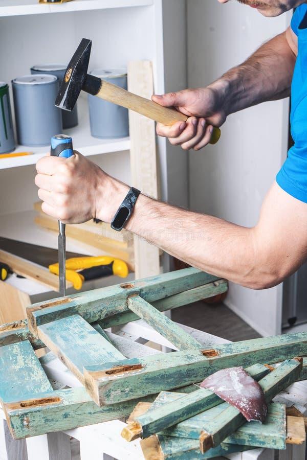 Carpinter?a: el amo de los muebles restaura el taburete viejo, dilapidado Primer de la mano de un hombre fotografía de archivo