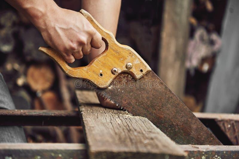 Carpintero con el handsaw imagenes de archivo
