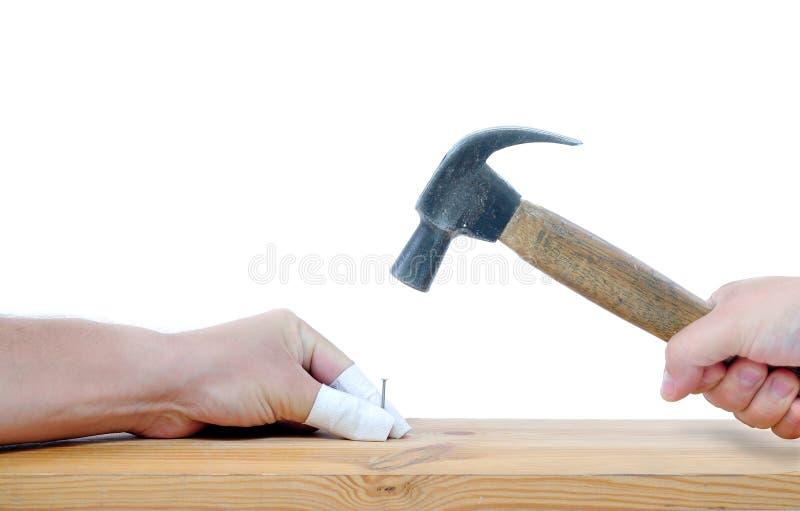 Carpintero con el martillo y los dedos dañados imagen de archivo libre de regalías