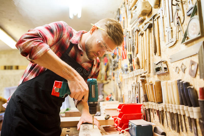 Carpintero con el tablón de la perforación del taladro en el taller imagen de archivo