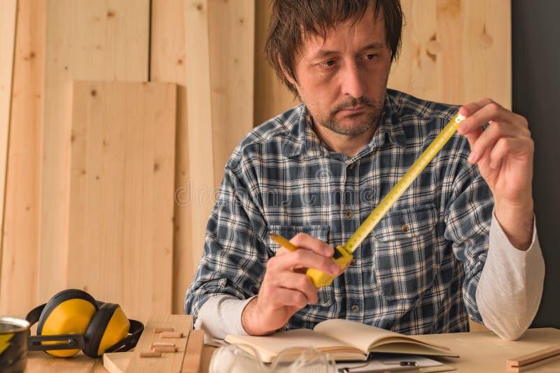 Carpintero con la herramienta de la cinta métrica foto de archivo