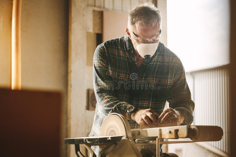 Carpintero con la máscara que trabaja en la máquina de la chorreadora de la correa fotografía de archivo