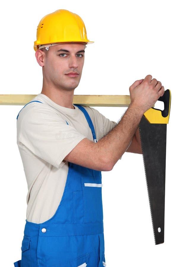 Carpintero con un handsaw. imagenes de archivo