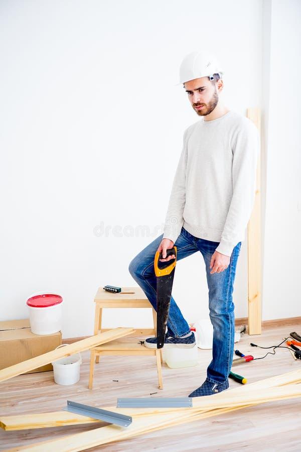 Carpintero con un handsaw foto de archivo