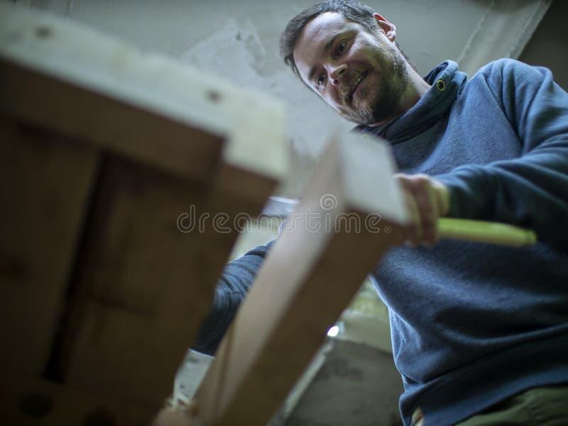 Carpintero con una barba que asierra un haz de madera con una sierra de mano un carpintero que asierra un pedazo de madera Visión fotos de archivo libres de regalías