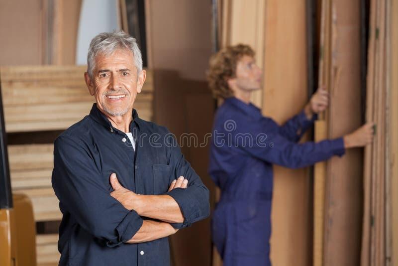 Carpintero confiado With Arms Crossed en taller foto de archivo