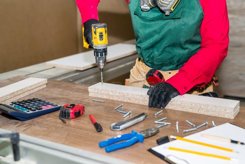 Carpintero de la mujer que hace el agujero en tablón de madera imagen de archivo libre de regalías