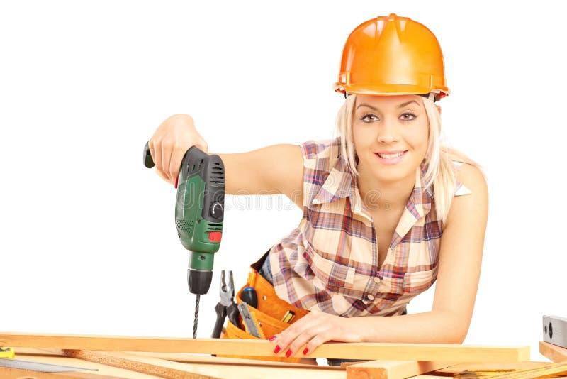 Carpintero de sexo femenino con el casco en el trabajo usando la máquina del sondeo a mano fotos de archivo libres de regalías