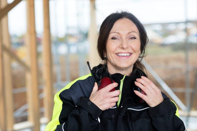 Carpintero de sexo femenino confiado With Ear Protectors en la construcción S fotos de archivo libres de regalías