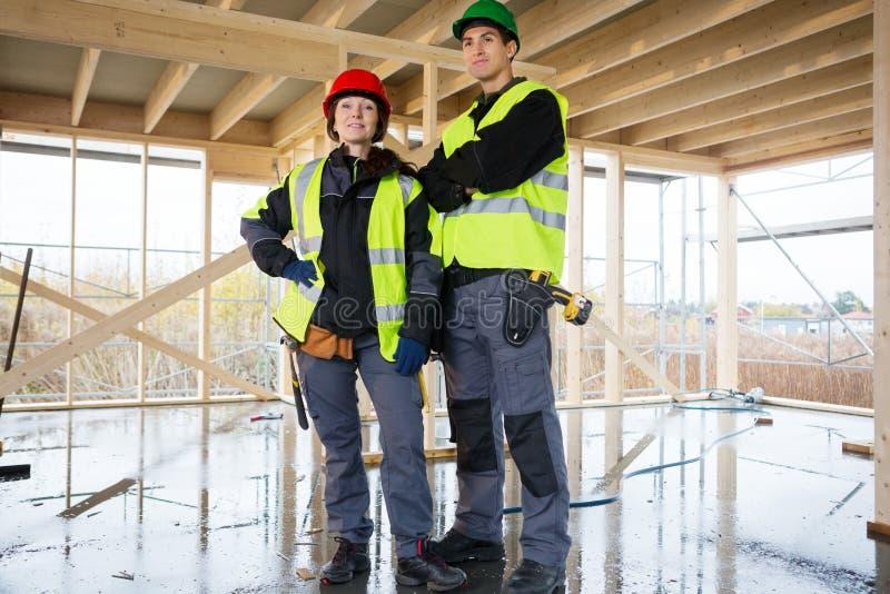 Carpintero de sexo femenino confiado Standing By Colleague en la construcción imagen de archivo