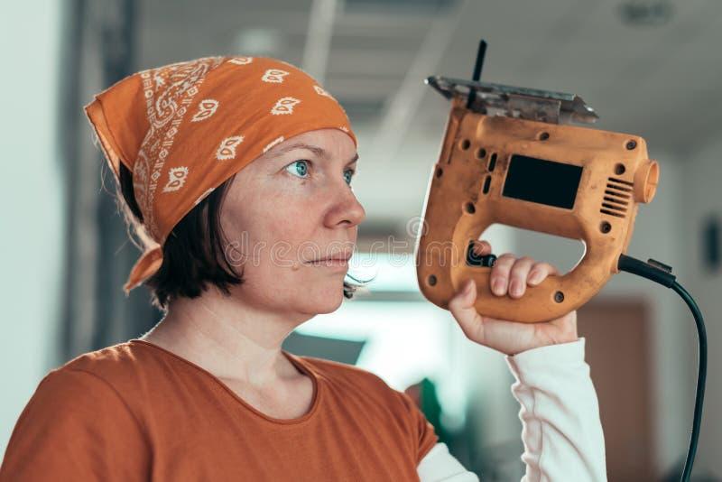 Carpintero de sexo femenino independiente con el rompecabezas eléctrico foto de archivo libre de regalías
