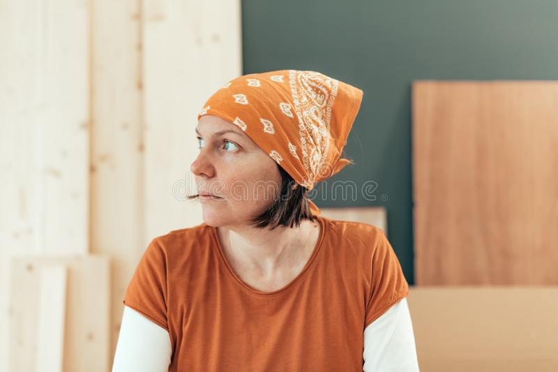 Carpintero de sexo femenino independiente que mira hacia fuera la ventana fotografía de archivo libre de regalías