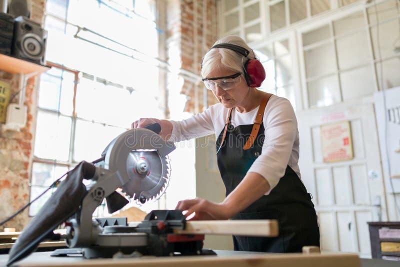 Carpintero de sexo femenino mayor que trabaja con una sierra circular imágenes de archivo libres de regalías