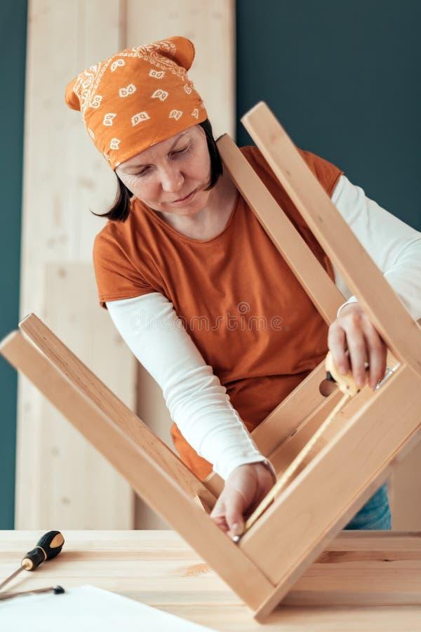 Carpintero de sexo femenino que repara el asiento de madera de la silla en taller imagen de archivo