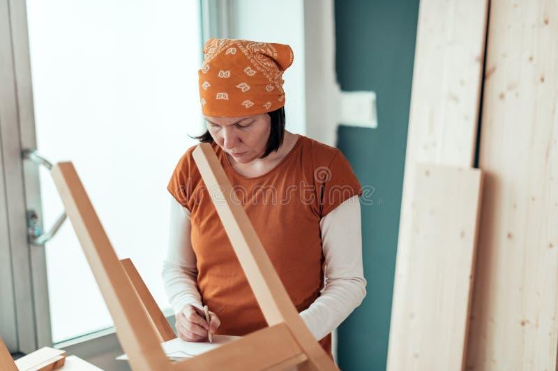 Carpintero de sexo femenino que repara el asiento de madera de la silla en taller foto de archivo libre de regalías