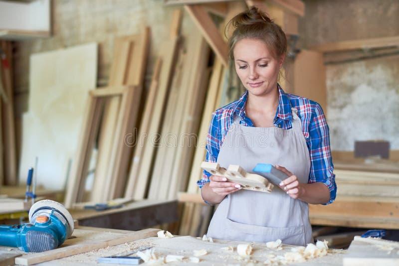 Carpintero de sexo femenino Sanding Wooden Part en taller imagen de archivo