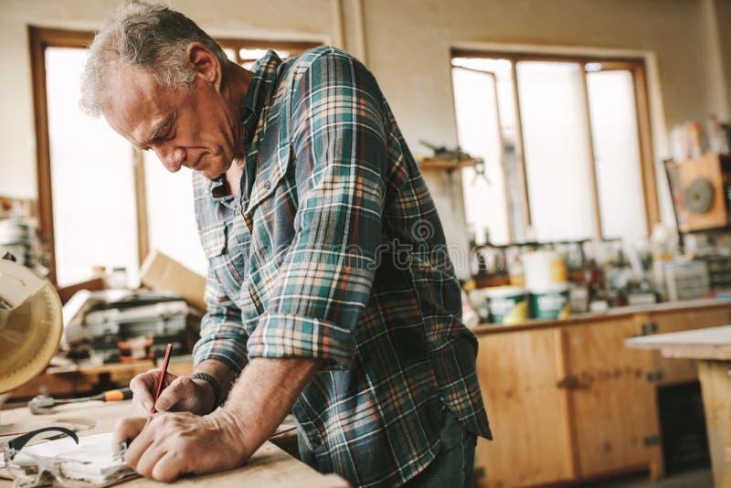 Carpintero de sexo masculino experto que hace dibujos en el tablero imagen de archivo