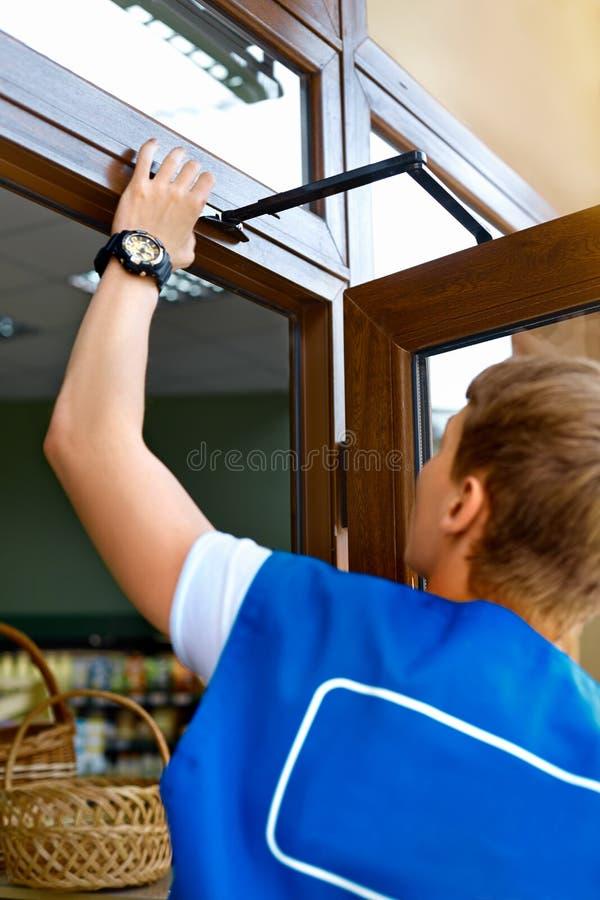 Carpintero de sexo masculino joven Repairing Door Window del retrato fotografía de archivo