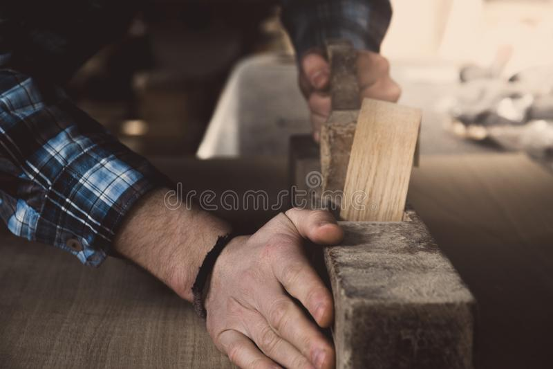 Carpintero del vintage que trabaja en la madera usando la alisadora antigua vieja del vintage retro de madera Fondo del taller foto de archivo libre de regalías