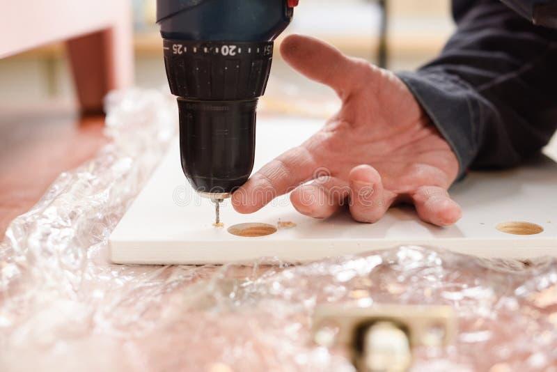 Carpintero en el trabajo Fabricación de los agujeros en puerta de madera con el taladro foto de archivo libre de regalías