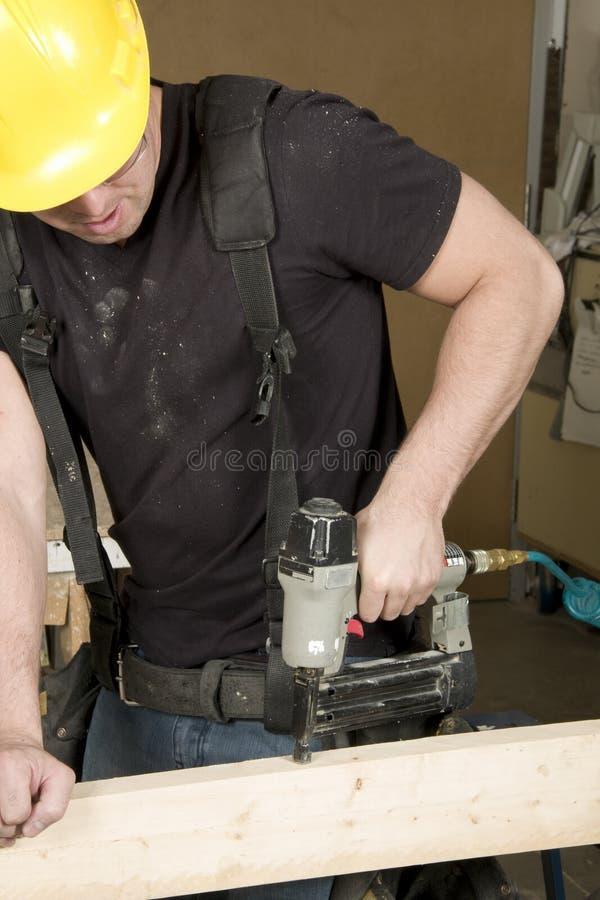 Carpintero en el trabajo sobre trabajo usando la herramienta eléctrica foto de archivo libre de regalías