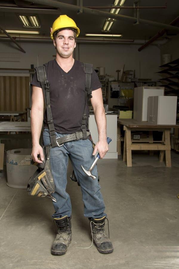 Carpintero en el trabajo sobre trabajo usando la herramienta eléctrica foto de archivo