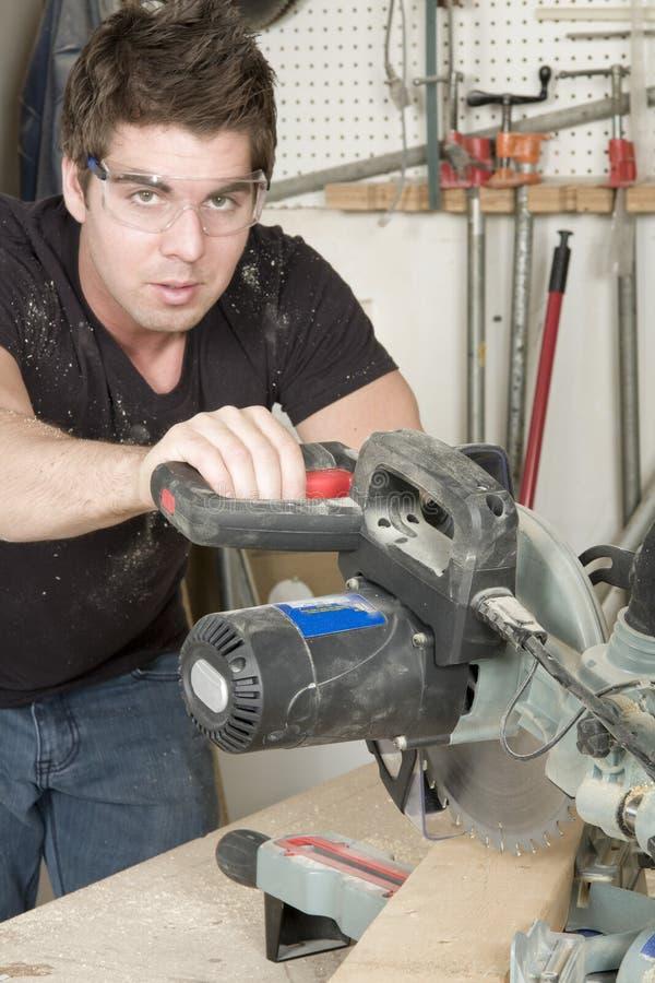 Carpintero en el trabajo sobre trabajo usando la herramienta eléctrica fotos de archivo libres de regalías