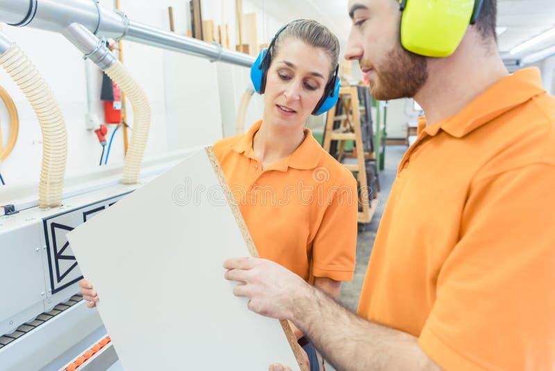 Carpintero en la fábrica de los muebles que examina el pedazo en el QA foto de archivo libre de regalías