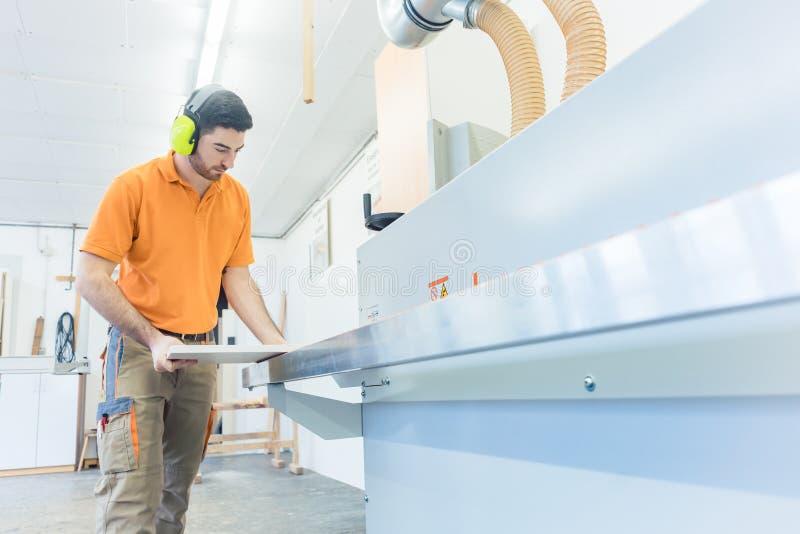 Carpintero en la fábrica de los muebles que trabaja en la máquina de la chapa foto de archivo libre de regalías