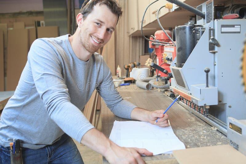 Carpintero en la tabla del drenaje en taller imágenes de archivo libres de regalías