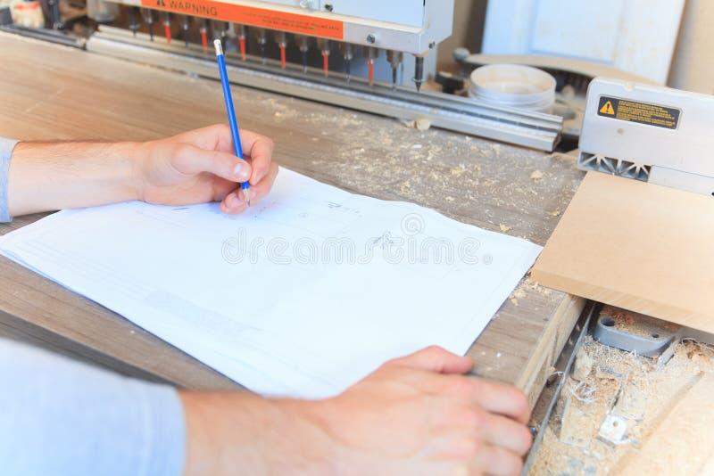 Carpintero en la tabla del drenaje en taller imagen de archivo