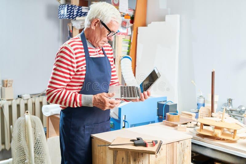 Carpintero envejecido con el ordenador portátil en taller fotos de archivo
