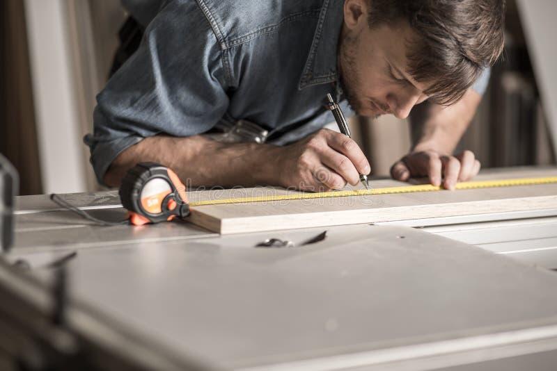Carpintero joven exacto durante trabajo imágenes de archivo libres de regalías
