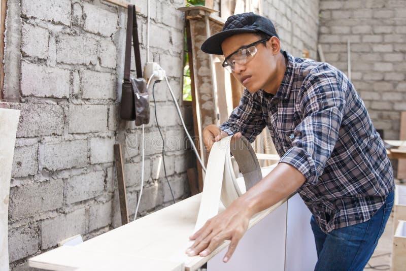 Carpintero joven que aplica el vinilo de madera en muebles fotografía de archivo libre de regalías