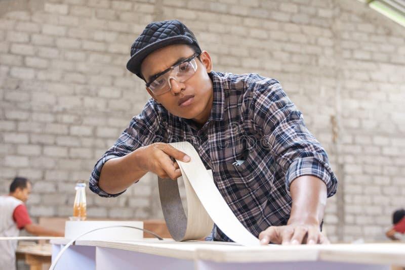 Carpintero joven que aplica el vinilo de madera en muebles foto de archivo