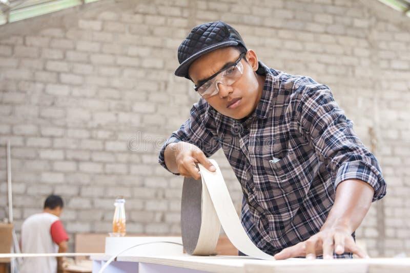 Carpintero joven que aplica el vinilo de madera en muebles imagen de archivo libre de regalías