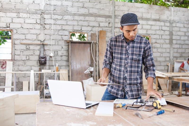 Carpintero joven que comprueba muestras materiales usando Internet en lapt fotos de archivo