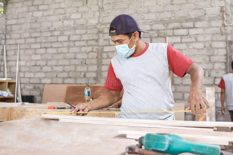Carpintero joven que mide al tablero de madera fotografía de archivo