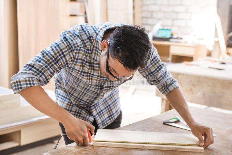 Carpintero joven que mide y que marca al tablero de madera imagen de archivo libre de regalías