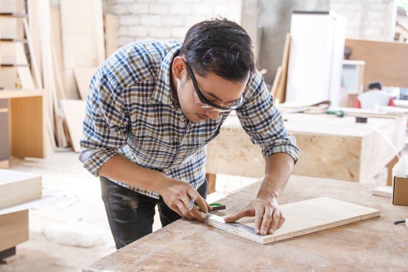 Carpintero joven que mide y que marca al tablero de madera imagenes de archivo