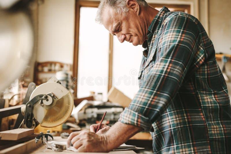 Carpintero mayor que planea su trabajo en la carpintería imagenes de archivo