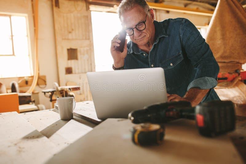 Carpintero mayor que trabaja en el ordenador portátil y el teléfono en su taller foto de archivo libre de regalías