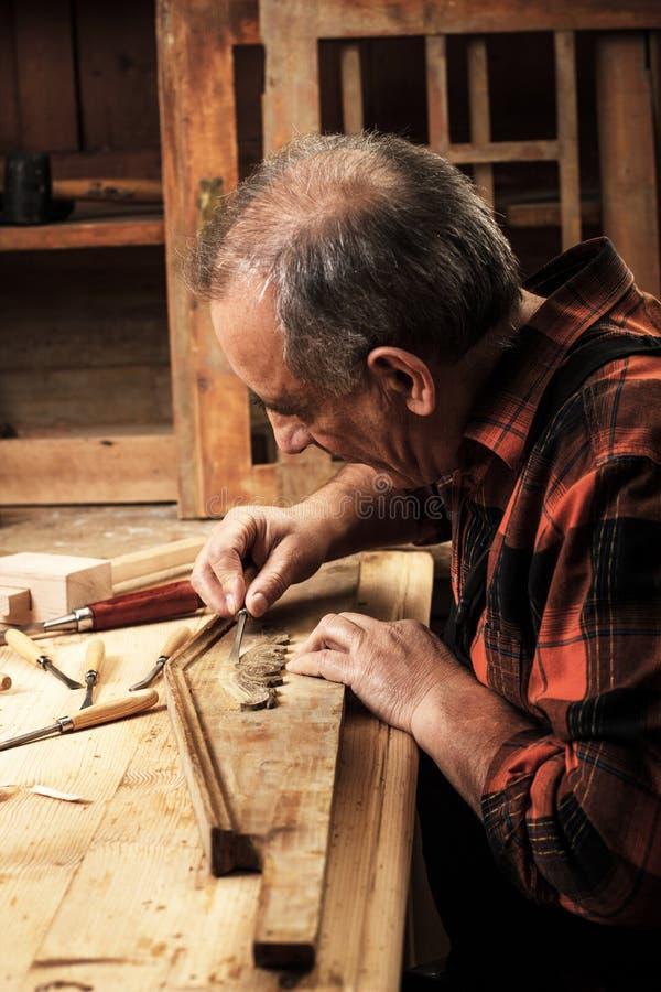 Carpintero mayor que trabaja en su taller imagen de archivo