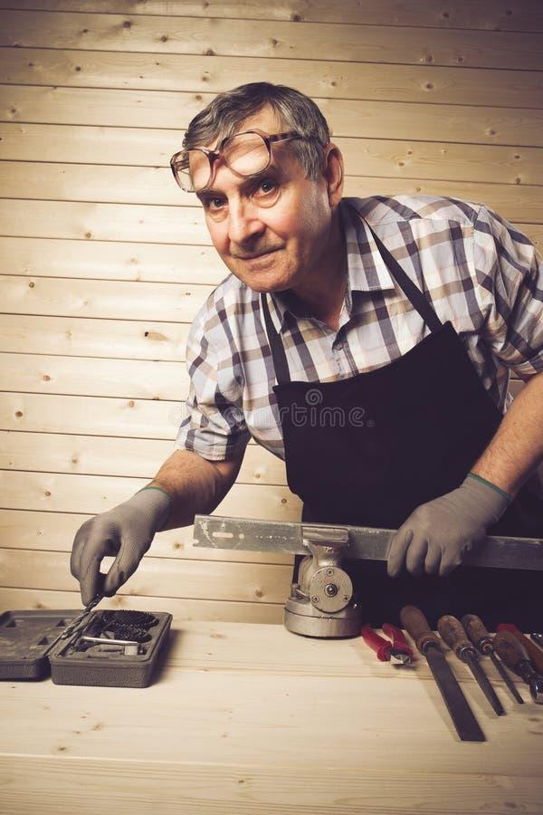 Carpintero mayor que trabaja en su taller fotos de archivo libres de regalías