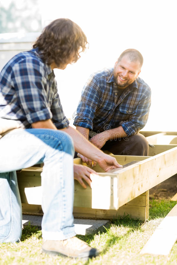 Carpintero Measuring Wooden Frame mientras que compañero de trabajo foto de archivo libre de regalías